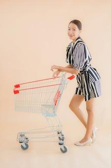 Portret piękna młoda azjatykcia kobieta z wózek na zakupy