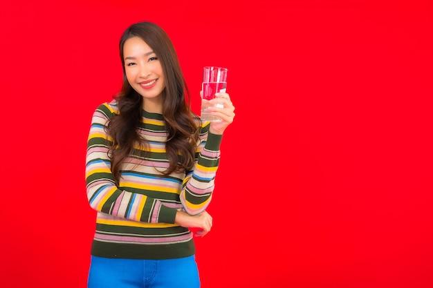 Portret piękna młoda azjatykcia kobieta ze szklanką wody pitnej na czerwonej ścianie