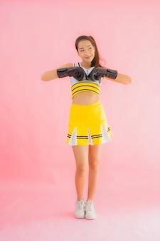 Portret piękna młoda azjatykcia kobiety chirliderka z bokserską akcją