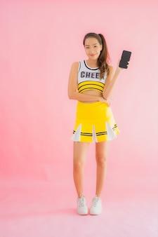 Portret piękna młoda azjatykcia kobiety chirliderka z mądrze telefonem komórkowym