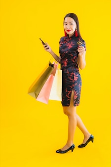 Portret piękna młoda azjatykcia kobiety odzieży chińczyka suknia z torba na zakupy