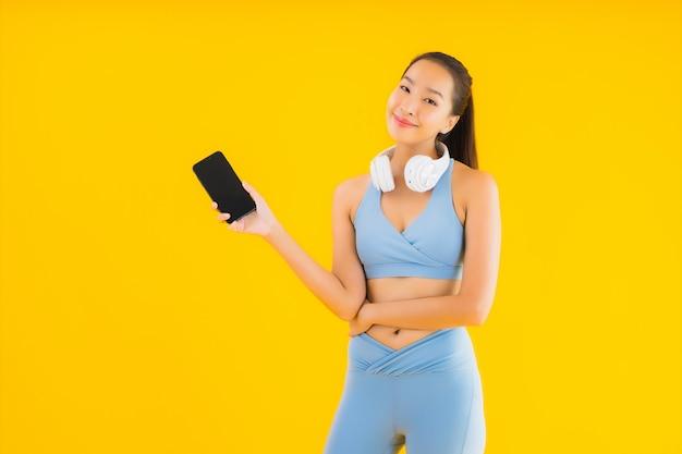 Portret piękna młoda azjatykcia kobiety odzieży sporta odzież z smartphone