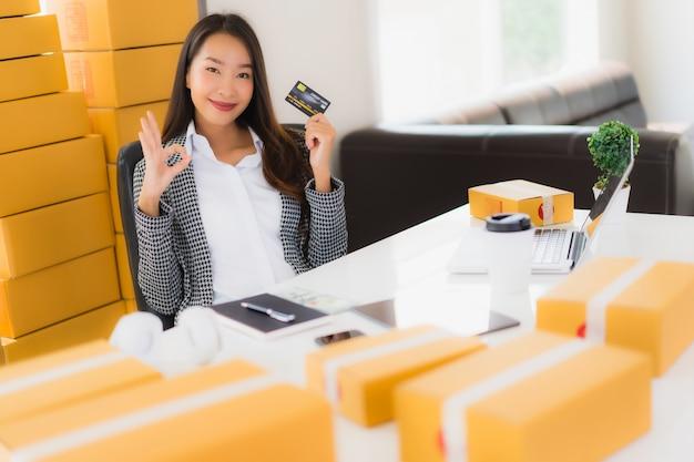Portret piękna młoda azjatykcia kobiety praca od domu z kredytową kartą i kartonem przygotowywającymi dla wysyłki zakupy