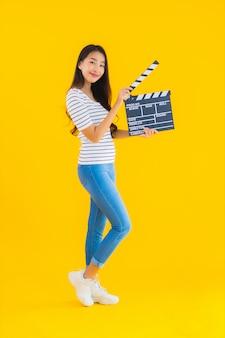 Portret piękna młoda azjatykcia kobiety przedstawienia clapper filmu deska