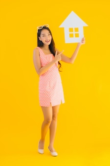 Portret piękna młoda azjatykcia kobiety przedstawienia domu lub domu znak