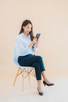 Portret piękna młoda biznesowa azjatykcia kobieta siedzi na krześle z smartphone