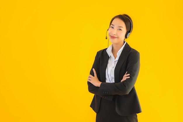 Portret piękna młoda biznesowa azjatykcia kobieta z hełmofonem lub słuchawki