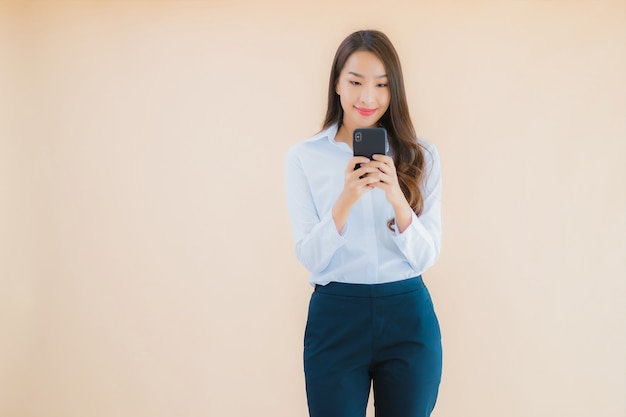 Portret piękna młoda biznesowa azjatykcia kobieta z inteligentny telefon komórkowy i filiżankę kawy