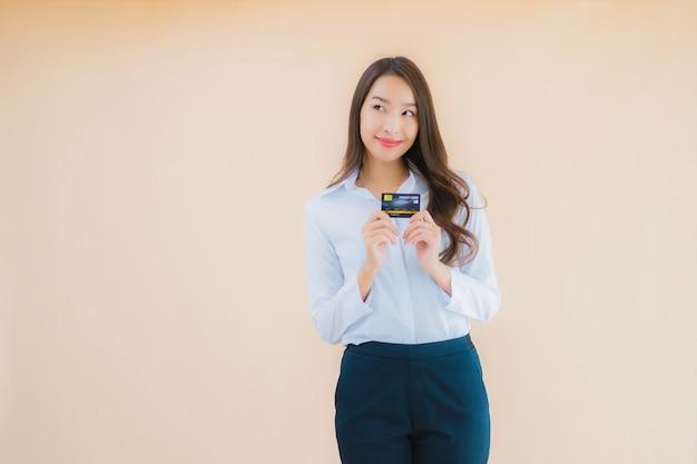 Portret piękna młoda biznesowa azjatykcia kobieta z kartą kredytową