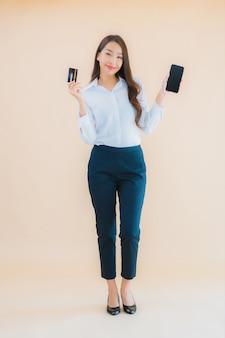 Portret piękna młoda biznesowa azjatykcia kobieta z telefonem i kartą kredytową