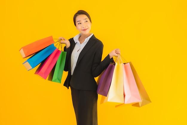 Portret piękna młoda biznesowa azjatykcia kobieta z torba na zakupy