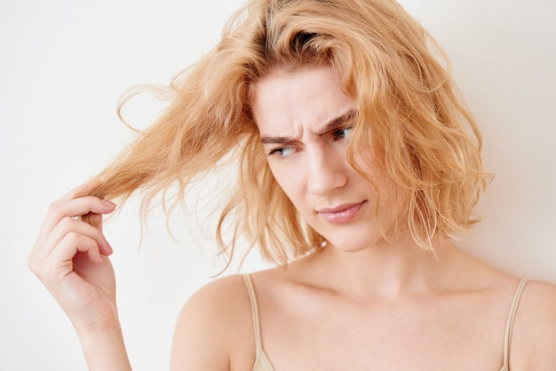 Portret piękna młoda blondynki kobieta trzyma kędziorek włosy w jej ręce z niezadowoloną wzburzoną twarzą