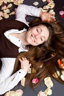 Portret piękna młoda brunetka kłama z różanymi płatkami