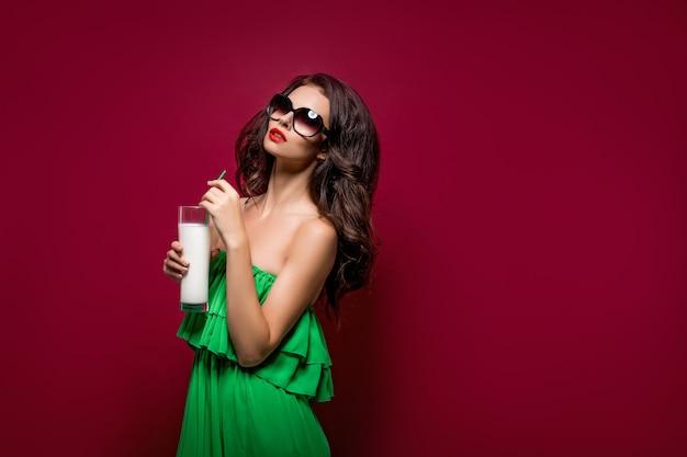 Portret piękna młoda brunetka w okularach przeciwsłonecznych i zieleni sukni z koktajlem