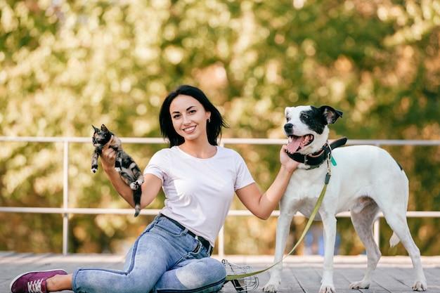 Portret piękna młoda brunetki dziewczyna z małym kotem i duży ogara psa siedzieć plenerowy w parku