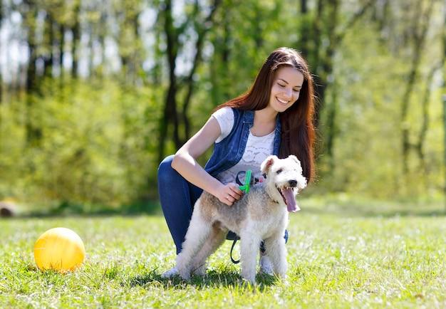 Portret piękna, młoda dziewczyna, czesanie swojego psa foksterier na zewnątrz