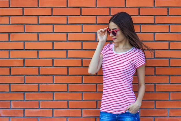Portret piękna młoda dziewczyna w czerwonych okularach przeciwsłonecznych nad czerwonym ściana z cegieł