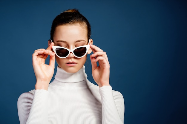 Portret piękna młoda dziewczyna w okularach przeciwsłonecznych na błękitnym tle