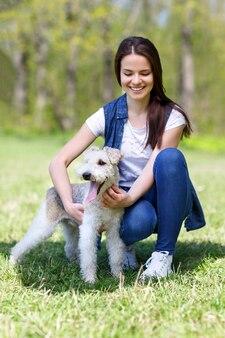 Portret piękna, młoda dziewczyna z psem foxterier na świeżym powietrzu w parku