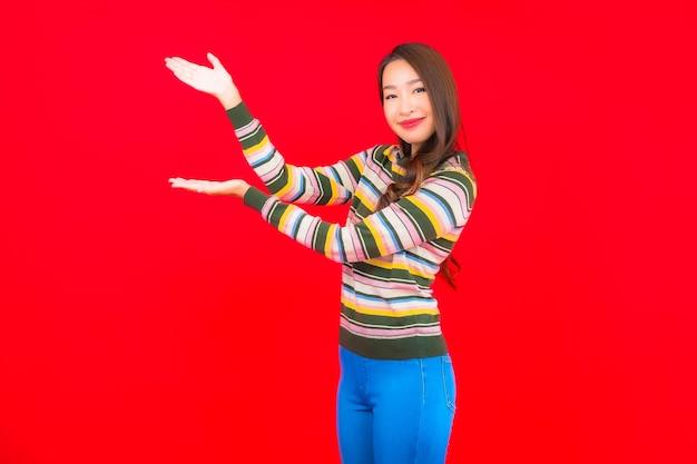 Portret piękna młoda kobieta azjatyckich uśmiech z działaniem na czerwonej ścianie na białym tle