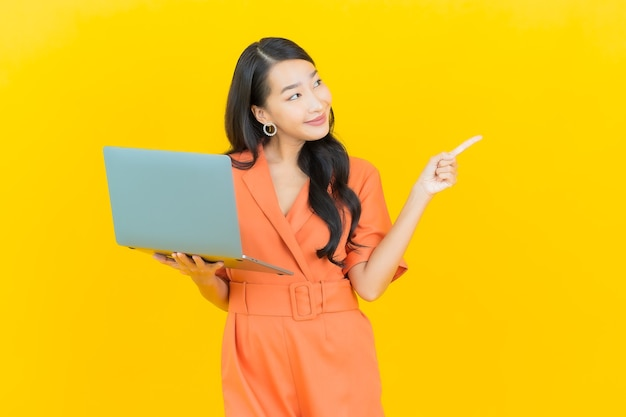 Portret piękna młoda kobieta azjatyckich uśmiech z laptopa na żółto