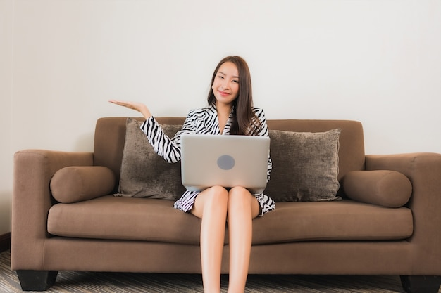 Portret piękna młoda kobieta azjatyckich używać komputera przenośnego na kanapie w salonie