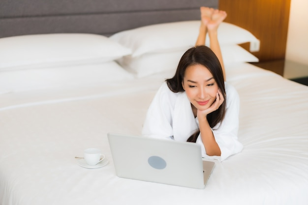Portret piękna młoda kobieta azjatyckich używać laptopa na łóżku we wnętrzu sypialni