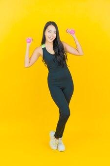 Portret piękna młoda kobieta azji nosić strój siłowni trzymając hantle