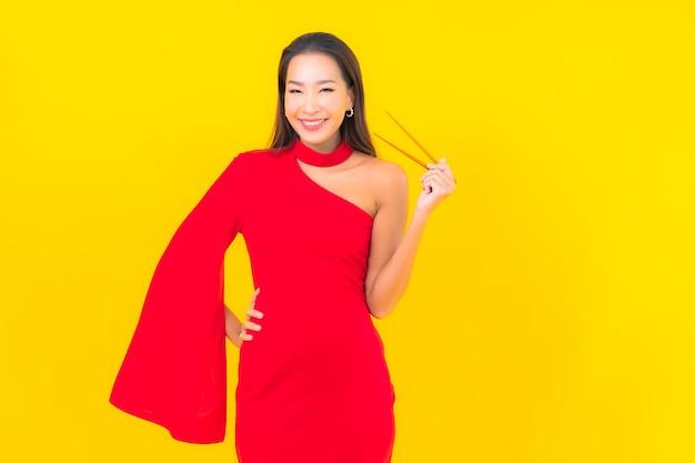 Portret piękna młoda kobieta azji z chopstick gotowe do spożycia