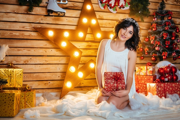 Portret piękna młoda kobieta która trzyma prezent dla nowego roku i bożych narodzeń.