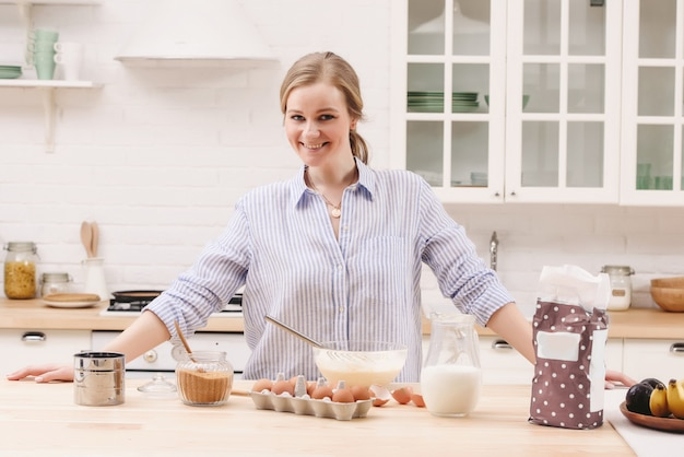 Portret piękna młoda kobieta ma śniadanie w kuchni.