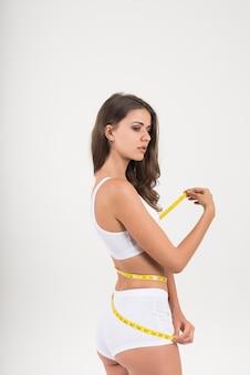 Portret piękna młoda kobieta mierzy jej postać rozmiar z taśmy miarą