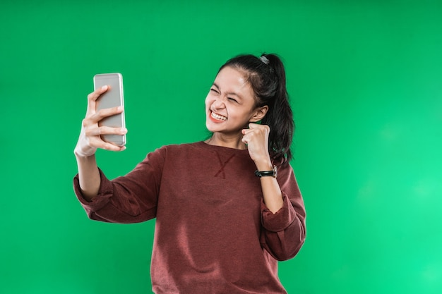Portret piękna młoda kobieta patrząc na coś na telefon z szczęśliwym wyrazem twarzy na zielonym tle