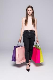 Portret piękna młoda kobieta pozuje z torba na zakupy odizolowywającymi na biel ścianie