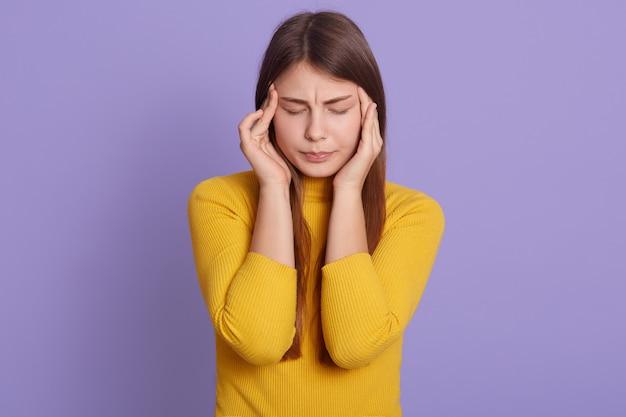 Portret piękna młoda kobieta trzymając ręce na świątyniach, cierpi na straszny ból głowy