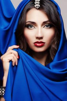 Portret piękna młoda kobieta w błękitnej tkaninie