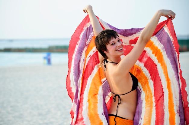 Portret piękna młoda kobieta w plaży. modelki w bikini zabawy na świeżym powietrzu.