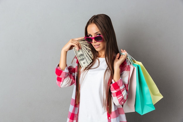 Portret piękna młoda kobieta w różowych szkłach, trzymający torba na zakupy i dolarowych banknoty