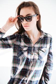Portret piękna młoda kobieta w szkockiej kraty koszula i okularach przeciwsłonecznych