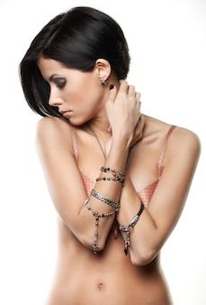 Portret piękna młoda kobieta z biżuterią na rękach