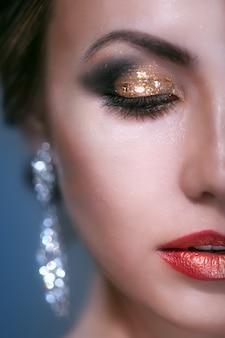 Portret piękna młoda kobieta z makijażem połysk na niebieskim tle soft focus