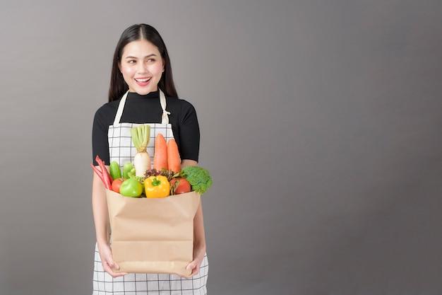 Portret piękna młoda kobieta z warzywami w sklep spożywczy torbie w pracownianym szarym tle