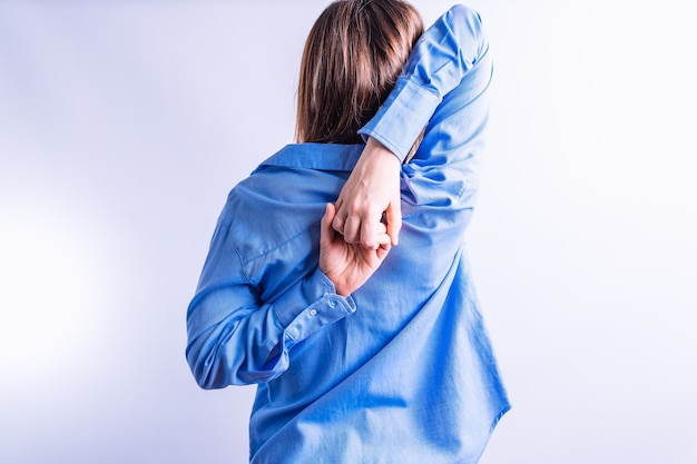 Portret piękna młoda kobieta zza rozciągania trzymając się za ręce za plecami. koncepcja stretch w biurze