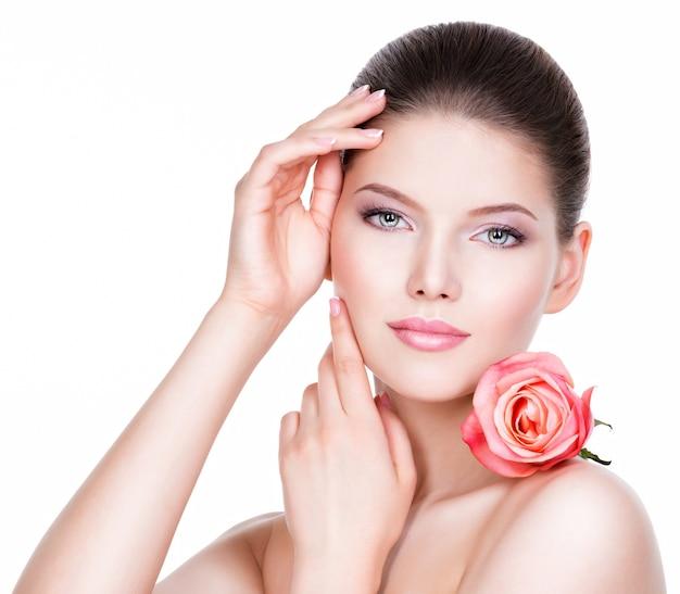 Portret piękna młoda ładna kobieta ze zdrową skórą i różową różą w pobliżu twarzy - na białym tle.