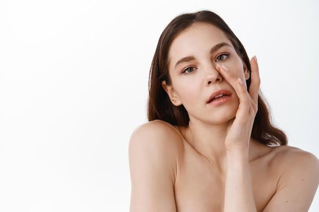Portret piękna modelka z naturalnym makijażem nago i dotykając jej twarzy. spa, pielęgnacja skóry i wellness