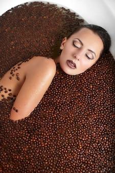 Portret piękna mody kobieta w jacuzzi z kawą. pielęgnacja ciała. jasny makijaż