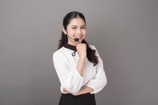 Portret piękna operator kobieta na szarości ścianie