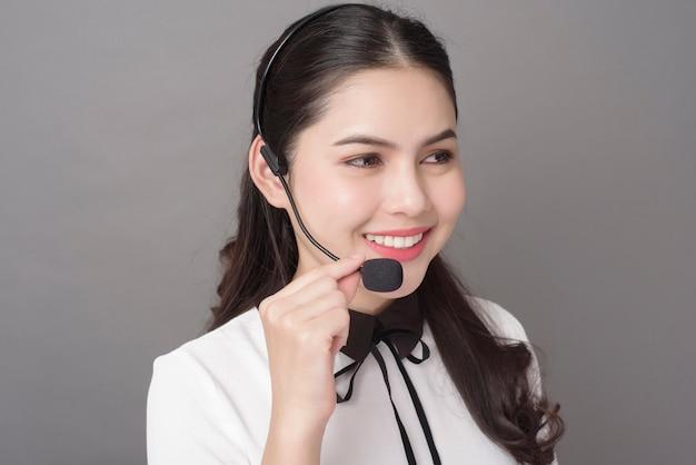 Portret piękna operator kobieta na szarym tle