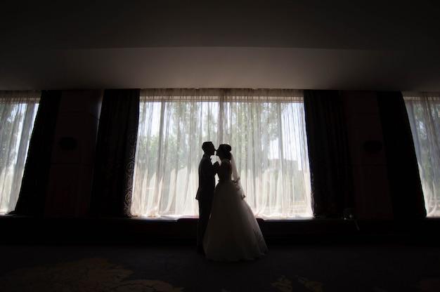 Portret piękna panna młoda i pan młody przeciw okno indoors