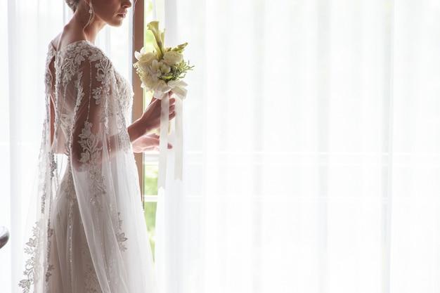 Portret piękna panna młoda trzyma bukiet blisko okno indoors